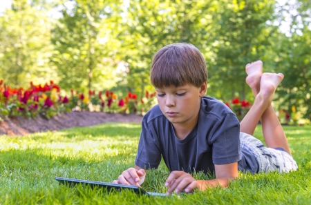 Boy using his laptop outdoor in park on grass Stok Fotoğraf