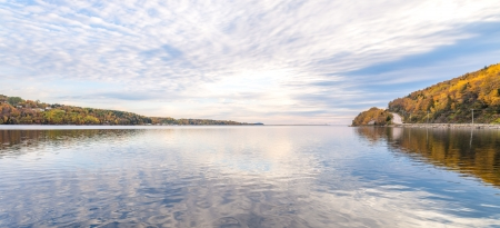 Panorama of lake in the autumn with reflections of clouds photo