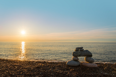 inukshuk: Inukshuk stones on ocean shore Stock Photo