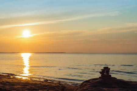 inukshuk: Inukshuk stones on ocean shore at sunset (Central Coastal Drive, Prince Edward Island , Canada) Stock Photo