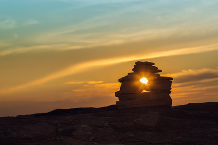 inukshuk: Close-up of Inukshuk  stones on ocean shore at sunset (Central Coastal Drive, Prince Edward Island , Canada) Stock Photo