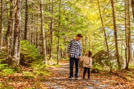 Brother and sister walking along park trail together Jeremy Bay Campground, Kejimkujik National Park, Nova Scotia, Canada Stock fotó