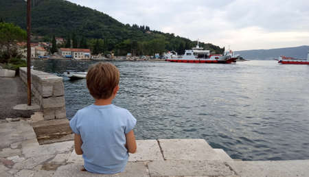 An unrecognizible caucasion boy is sitting at coast and watching for ferry-boats. Stock Photo