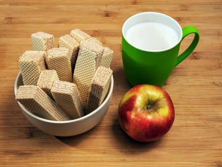 A bowl of neapolitan waffles, red apple and green mug of milk on a wooden table. Close-up. High angle view. Still life