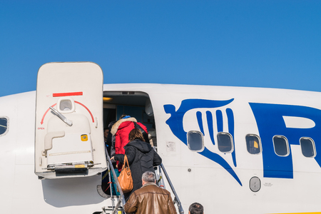 BOLOGNA, ITALY – FEBRUARY 2016: Passengers boarding Ryanair jetliner at the Bologna airport, Italy to Bucharest, Romania. Ryanair Ltd. is an Irish low-cost airline headquartered in Swords, Dublin, Ireland. Stock Photo