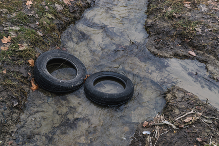 Two tires in a river, pollution concept.