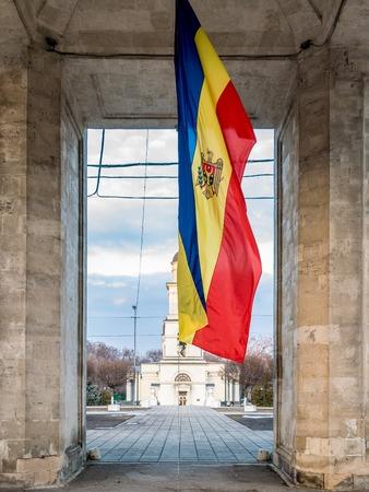 The flag of Moldova beneath the Triumph Arch in Chisinau, Moldova.