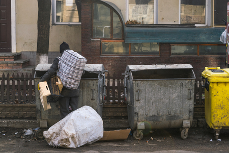 An unidentified man looking for something in the garbage can. Stock Photo