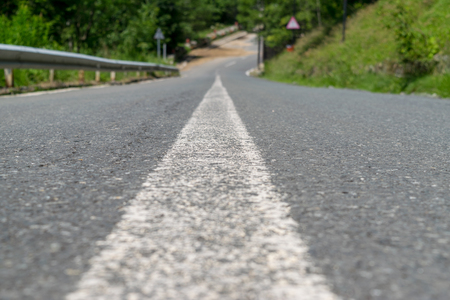 A white line in the middle of the road for as a delinitation of it. Stock Photo