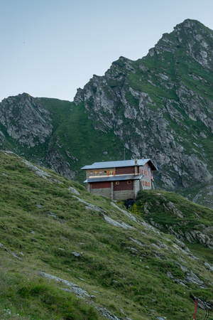 The Transfagarasan mountains and a cabin nearby them.