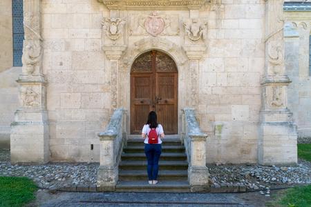 Girl standing in front of the Roman-Catholic Cathedral Saint Michael inside the Citadel Alba-Carolina in Alba Iulia, Romania.