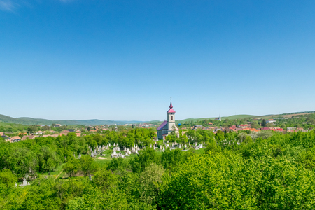 Beautiful rural church with a cemetery in a small village on a sunny day with blue sky Stock Photo