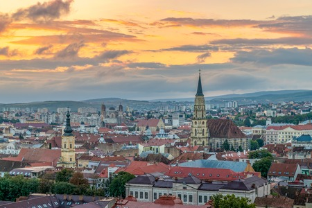 The old city of Cluj-Napoca with the Franciscan Church and St. Michaels Church viewed from Cetatuia Park at sunrise in Cluj-Napoca, Romania Standard-Bild