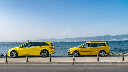 Yellow taxi cars on a street at see with water in the background. Yellow taxi cars on a beautiful sunny summer day with blue sky. Yellow taxi cars waiting.