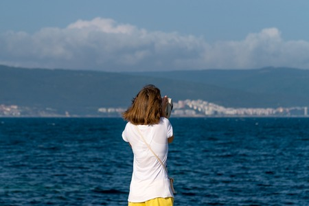 An unidentified girl looking through a tower viewer at sea in Nessebar, Bulgaria. A girl looking through a coin binocular, free use viewer, outdoor viewer. Banque d'images