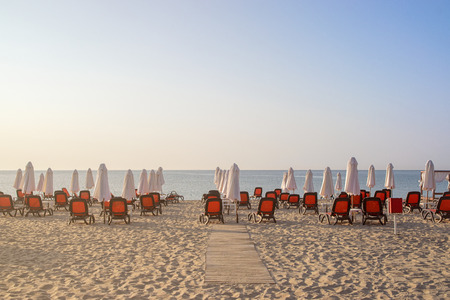 Chairs and umbrellas on a beautiful beach at sunrise in Sunny Beach on the Black Sea coast of Bulgaria.