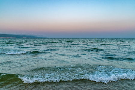 Waves at the beach at sunset in Sunny Beach on the Black Sea coast of Bulgaria.