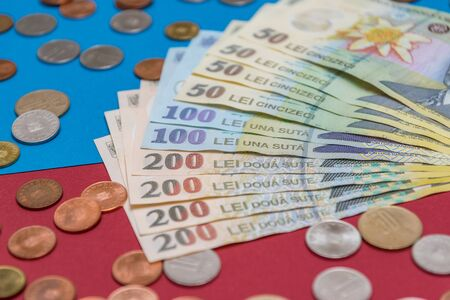 Romanian banknotes and coins on a blue and red background. Coloseup of RON, Romanian Currency. Romanian RON, Lei Banknotes issued by BNR, National Bank of Romania. Romania Finance and economy concept.