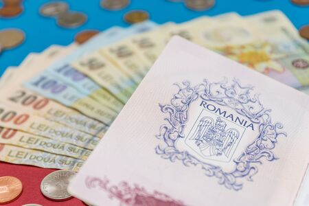 Romanian concept. The Romanian passport and Romanian banknotes/coins on a blue and red background. Coloseup of Romanian Passport and Romanian currency. Romania Finance and economy concept. Foto de archivo