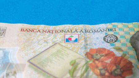 Romanian banknotes on a blue and red background. Coloseup of RON, Romanian Currency. Romanian RON, Lei Banknotes issued by BNR, National Bank of Romania. Romania Finance and economy concept.
