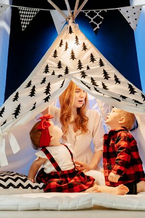 Cute young cheerful mom plays children under the tent