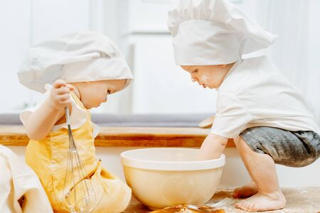 Side view of a cute little cook children in hats Stockfoto
