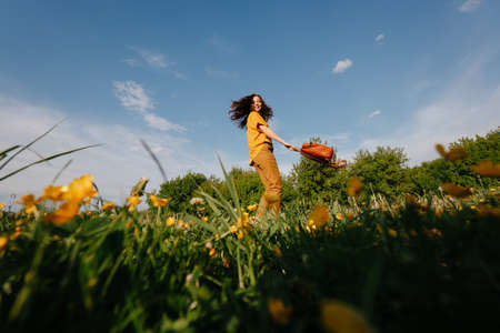Dark-haired young woman runs joyfully in a green field with yellow flowers against a blue sky with clouds. Vacation and allergy for pollen concept.