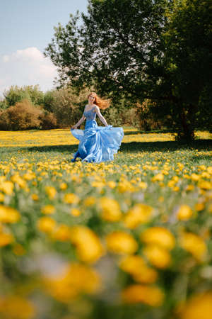 A happy fairy-tale girl in an airy blue dress runs joyfully along the green lawn in the park. Blooming field in yellow dandelions. Allergy free concept.
