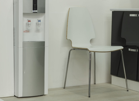 Stock Photo   White Chair Stands Next To A Water Dispenser