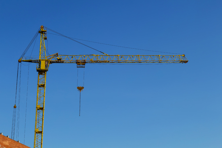 unfinished building: Tower crane at the construction site Stock Photo