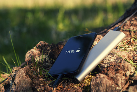 A portable charger charges the smartphone. Power Bank with cable against the background of wood.