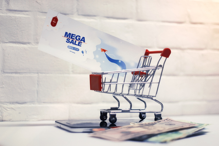 Online sale concept. Shopping cart and flyer with tablet and money on the background of a brick wall.