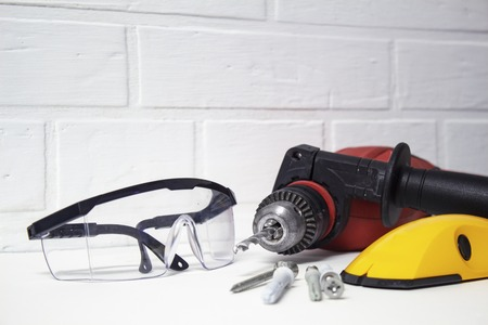 Professionelles Werkzeug zum Bohren. Elektrische Bohrmaschine mit Schutzbrille auf einem Backsteinmauerhintergrund. Standard-Bild