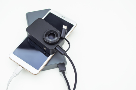 Portable charging gadgets. Smartphone with action camera connected to the power bank on a white background.