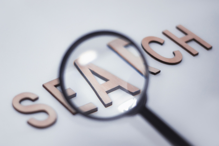 Concept on the topic of Search. Magnifying glass with black handle and wooden letters on a white background