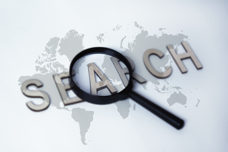 Concept on the topic of Search. Magnifying glass with global World Map and wooden letters on a white background