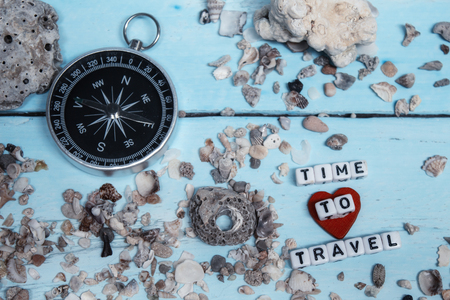 Time to Travel. Idea for tourism with compass on the sand with corals on the wooden background