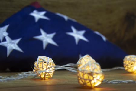 American flag with Garland on a wooden background for Memorial Day and other holidays of the United States of America.