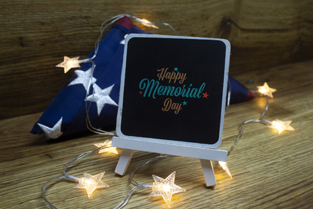 American flag with Chalk Board and Garland on a wooden background for Memorial Day and other holidays of the United States of America.