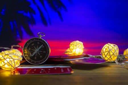 Time to Travel. Idea for tourism with passport, tickets and compass with garlands against the backdrop of a beautiful sunrise, palm trees and the sea. Concept on the theme of flights.