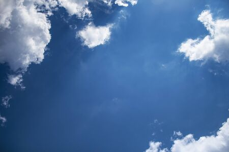 Blue sky background with clouds and sunlight.