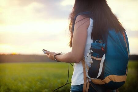 Girl with a backpack on a journey. Tourist holds in her hand a smartphone and a Power Bank on the background of the forest and sunset.