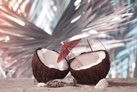 Time to travel. Two halves of a coconut with an umbrella on the beach against the backdrop of a palm leaf. Concept on the topic of tourism