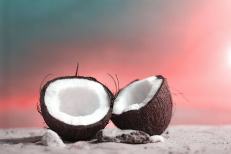 Time to travel. Two halves of coconut on the beach against the backdrop of a beautiful sunset. Concept on the topic of tourism.