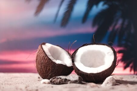 Time to travel. Two halves of coconut on the beach at sunset time against the backdrop of palm trees and sky. Concept on the topic of tourism. Banco de Imagens