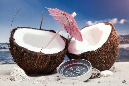 Time to travel. Two halves of a coconut with an umbrella and a compass on the beach against the background of the sea and sky. Concept on the topic of tourism Stock fotó