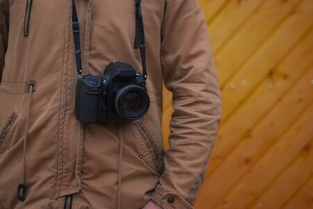 A photographer with a camera around his neck on a wooden background