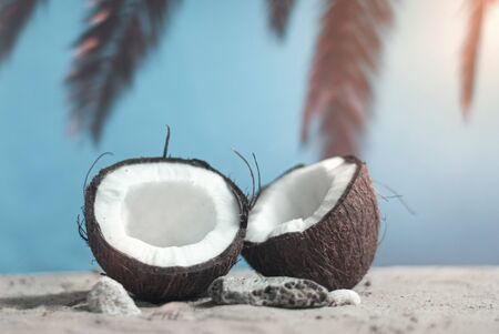Time to travel. Two halves of coconut on the beach at sunset time against the backdrop of palm trees and sky. Concept on the topic of tourism