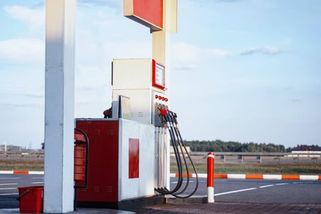 Gas station close-up with colored fuel hoses background on the road and car