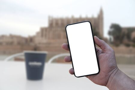 Mock Up smartphone with a white screen in hand, on the background of a cup with a castle coffee on the island of Palma de Mallorca in Spain